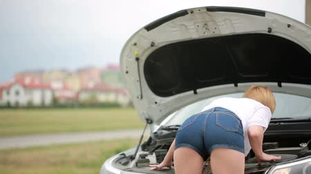eşek : woman opens the hood Broken car. girl looks at a damaged engine. Stok Video