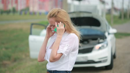meteliksiz : woman and broken car calling for help on cell phone. broken car on the road