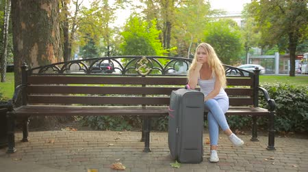усталость : sad girl sitting on the bench with a suitcase.