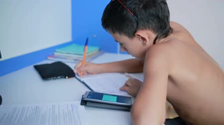 honesto : Teenage boy doing homework using a cell phone. natural video