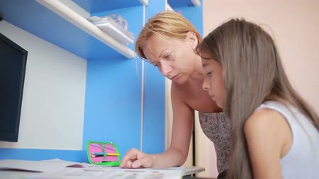 домашнее задание : Mom helping her daughter do homework. Girl makes lessons Стоковые видеозаписи
