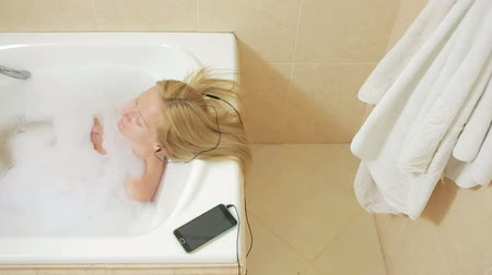 честный : beautiful woman taking a bath and listening to music on headphones. cell phone