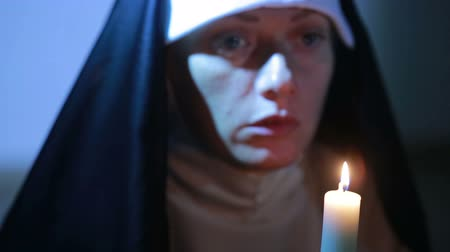 dua eden : woman nun praying at night. burning candles. Woman in clothes nuns