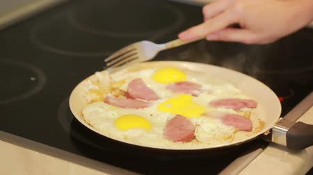 poached egg : fried eggs and ham in a pan for breakfast. Cooking