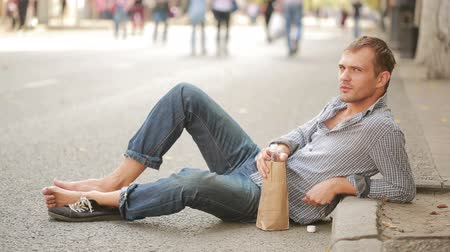 hívó : drunk man lying on the pavement outside. man drinking beer from a paper bag Stock mozgókép