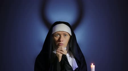 repentance : Halloween. nun prays. shadows in the form of devil. exorcism