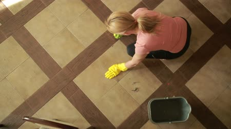 cleaning products : woman cleaning the floor. girl in gloves cleans the kitchen