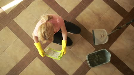 besom : woman cleaning the floor. girl in gloves cleans the kitchen