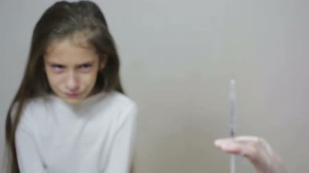 paediatrician : little girl is afraid of the doctor with a syringe. baby cries afraid injection
