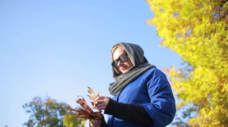 başörtüsü : beautiful woman in sunglasses in autumn park. Keeps hands Yellow leaves