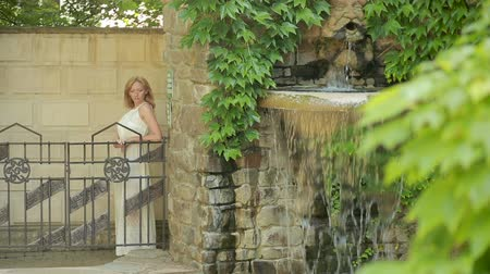 bogaty : beautiful blonde girl walking through the old park with a fountain.