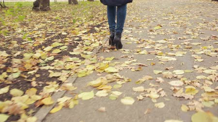 camurça : Woman walking through leaves. autumn Park