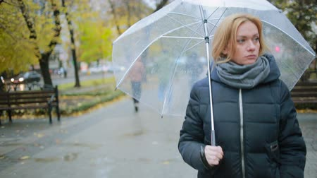 lonely : girl in the rain with an umbrella. autumn woman walking down the street Stock Footage