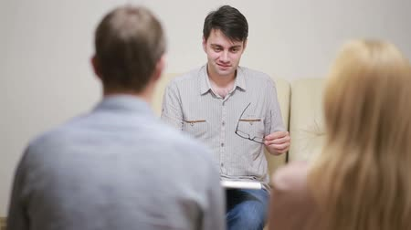 reconcile : male psychologist helping worried young couple. family therapy. angry people