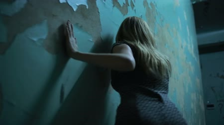 susto : exhausted girl goes hand in wall, physical violence concept Vídeos