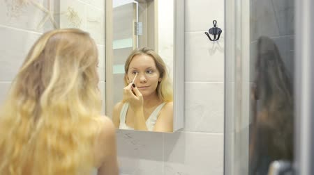 rubs : Beautiful young woman is doing makeup in front of the mirror.