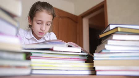uniforme : little girl in school uniform is reading a book, sitting between piles of books Vídeos