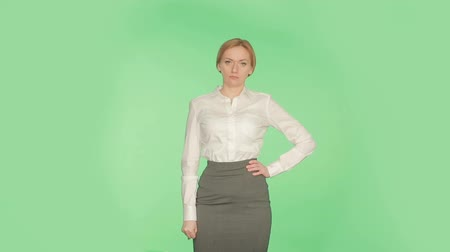 hostility : Body language. Beautiful blonde girl in a white blouse on a green background.
