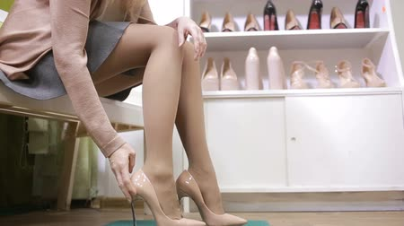 high heels : beautiful girl choosing a pair of high heels shoes. Beautiful legs.