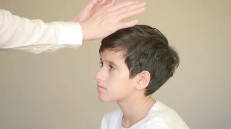 целебный : Receiving healing energy, boy with female hands hovering over his forehead
