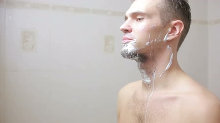 barbear : guy shaving off his beard with a razor in the bathroom and smiling
