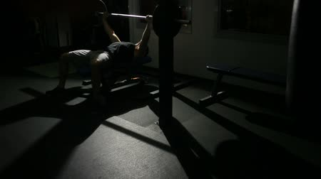 lökés : athlete man does bench press from chest exercise in gym hall