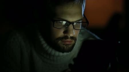débito : guy with glasses and a sweater with a tablet in the dark