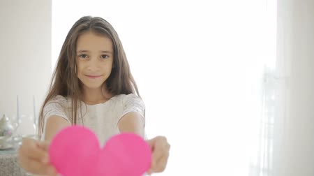 shy girl : Happy smiling girl showing red heart. Valentines Day Stock Footage