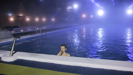 champagne pool : Woman at night in the pool with thermal water with a glass of champagne