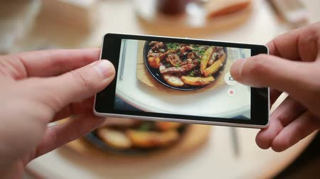pic : Trendy man in a restaurant make photo of food with mobile phone camera