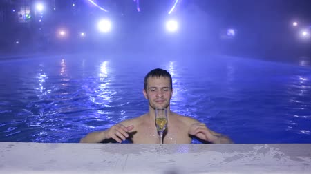 champagne pool : Happy man Swim in the pool at night and drinking from glasses. Thermal source