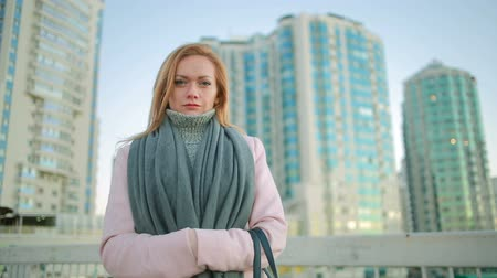 başörtüsü : girl in a pink coat walks on a modern city on the background of skyscrapers