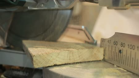 miter saw : hand man sawed wooden board using a miter saw with laser