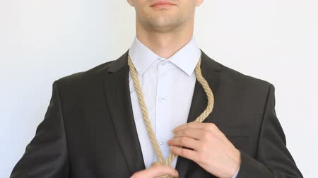 unloved : Businessman adjusting a noose rope like tie, going on not your favorite job, Stock Footage