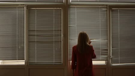 persiana : woman looking out the window through the blinds to the street, spying. suspected Stock Footage