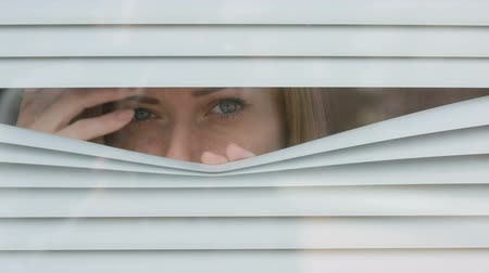 alarmed : woman looking out the window through the blinds to the street, spying. suspected Stock Footage