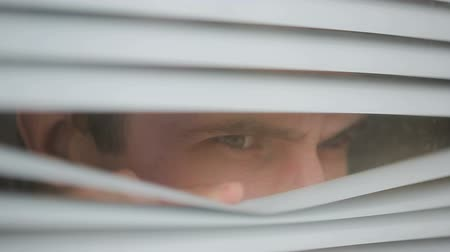 alarmed : man looking out the window through the blinds to the street, spying. suspected
