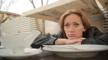 ношение : woman at a table in a cafe, waiting for him to eat. Empty plates