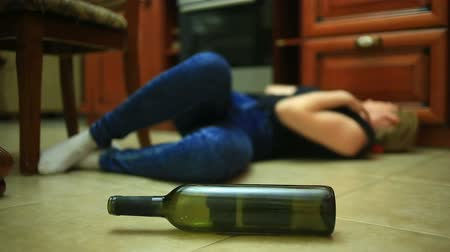 beyaz şarap : Woman drinking alcohol, woman with bottle in hands. Empty bottle of alcohol under the background of a woman lying on the floor.