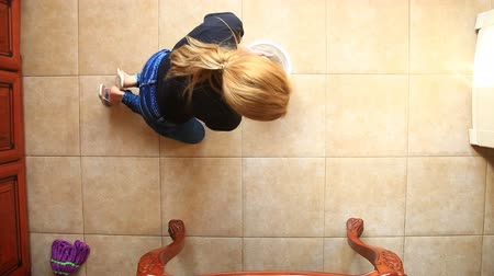 cleaning equipment : A woman washes the floor in the kitchen holding a blue rag. Dipping a rag in a colorful bucket, view from above Stock Footage