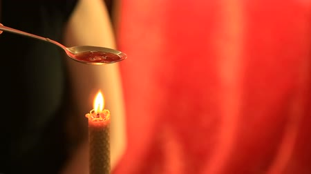 foretell : Divination with candle. woman pouring wax into the water Stock Footage
