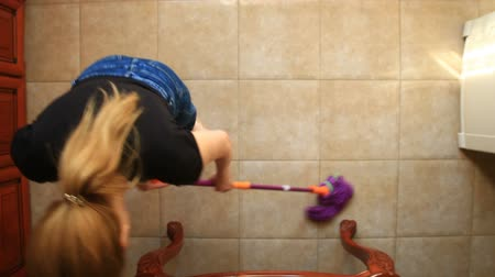 домохозяйка : A woman washes the floor in the kitchen with a mop. Dipping a rag in a colorful bucket, view from above