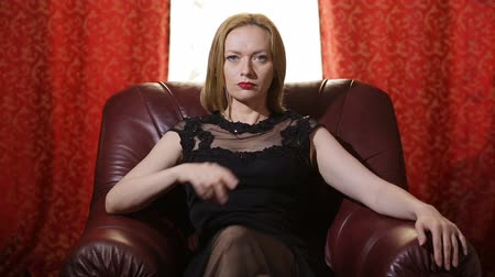 főnök : A fatal woman in a black dress and a red lipstick on her lips sits in a leather chair and arrogantly looks into the camera . Gestures to silence, to finish. Stock mozgókép