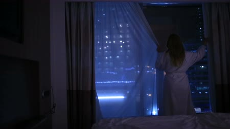 unveil : A young woman closes the curtains at night and goes to bed Stock Footage