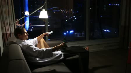 inebriated : The man is resting at home on the couch at night, drinking beer and watching TV, against the background of a large ponamramnogo window overlooking the night city