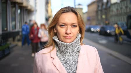 um : A woman in a pink coat and sweater stands in the middle of a crowded street and looks at the camera Stock Footage