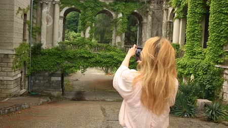 peluş : A tourists girl takes pictures of the beautiful collonade of an old castle twisted with ivy. Stok Video