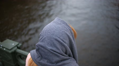 oneself : A woman in a coat stands on a bridge and looks down at the black water.