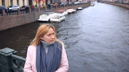 parlayan : Woman in pink coat and sweater stands on bridge over water background and looks at camera Stok Video