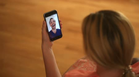 conferencing : A woman is holding a video chat with a man on a smartphone. They talk fun and laugh